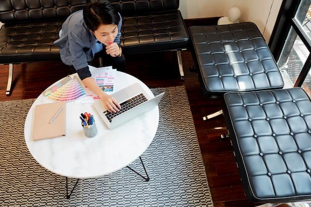 Vrouwenontwerper die online aan laptop werken Premium Foto