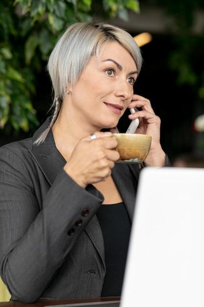 Vrouwenoudoor die van koffie genieten en bij telefoon spreken Gratis Foto