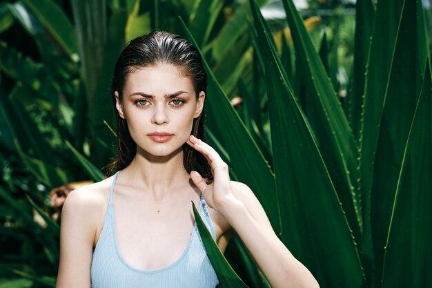 Vrouwenportret, groene bladeren van palmbomen, mooi gezicht Premium Foto