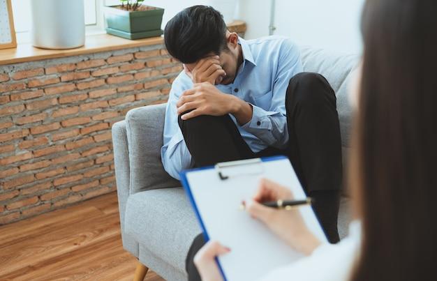 Vrouwenpsychiater het schrijven symptoom van aziatische jonge man patiënt terwijl hij zitting op bank Premium Foto