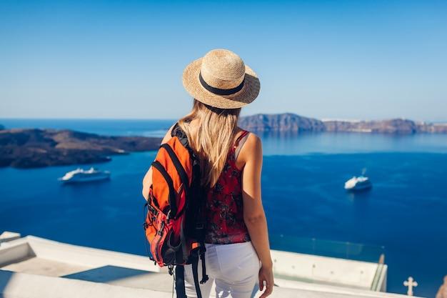 Vrouwenreiziger die in caldera van fira of thera, santorini-eiland, griekenland bekijken. toerisme, reizen, vakantie concept Premium Foto
