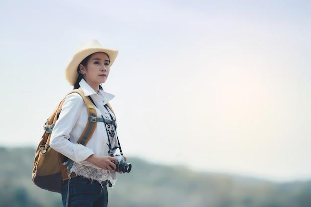 Vrouwenreiziger die met rugzak bij bergenlandschap wandelen Gratis Foto
