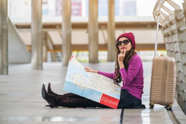 Vrouwenreiziger die reiskaart in luchthavengang bekijken met zak of bagage. Premium Foto