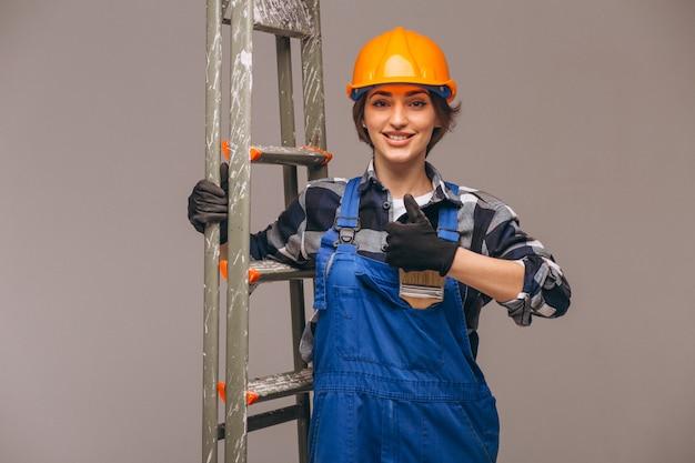 Vrouwenreparateur met ladder in een geïsoleerd uniform Gratis Foto