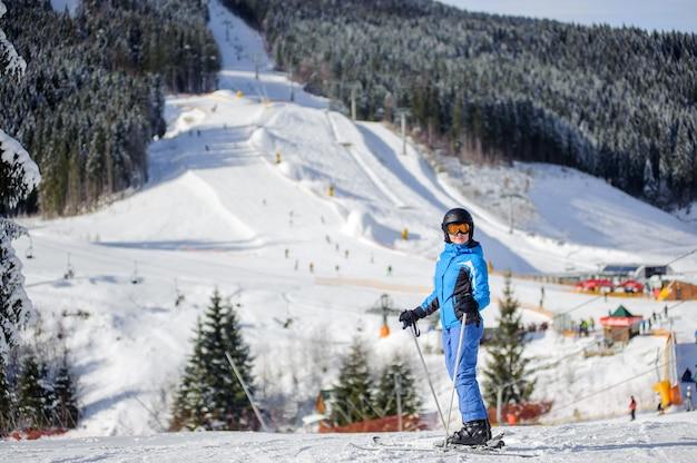 Vrouwenskiër tegen skihellingen en skilift op achtergrond Premium Foto