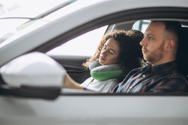 Vrouwenslaap in een auto op een autohoofdkussen Gratis Foto