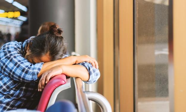 Vrouwenslaap in een luchthaventerminal met soft-focus en meer dan licht op de achtergrond Premium Foto