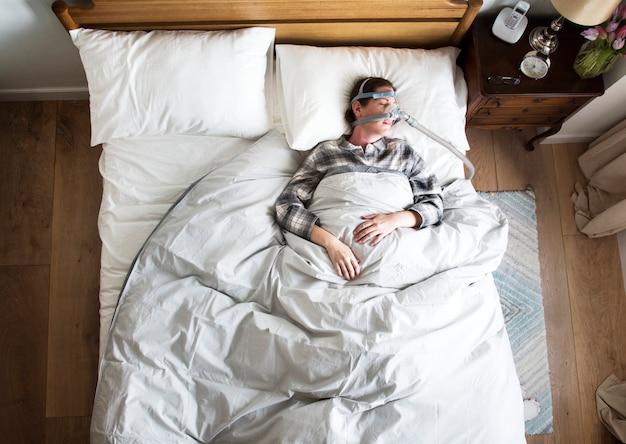 Vrouwenslaap met een anti-snurkerend masker Premium Foto