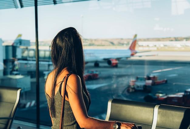 Vrouwentoerist die zich met bagage het letten op venster op luchthaven bevinden die op zijn vlucht wachten. Premium Foto