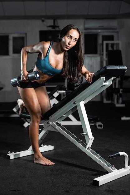 Vrouwentreinen in de sportschool. atletische vrouw traint met halters, pompen zijn biceps Premium Foto
