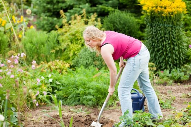 Vrouwentuinman die de grond graven Premium Foto