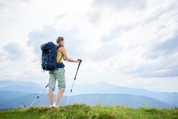 Vrouwenwandelaar die op grasrijke heuvel wandelen, die rugzak dragen, die trekkingsstokken in de bergen gebruiken Premium Foto
