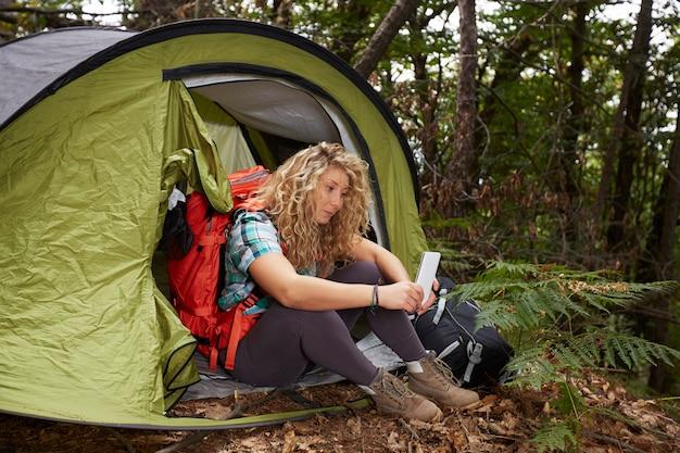 Vrouwenwandelaar met tent in het bos Premium Foto