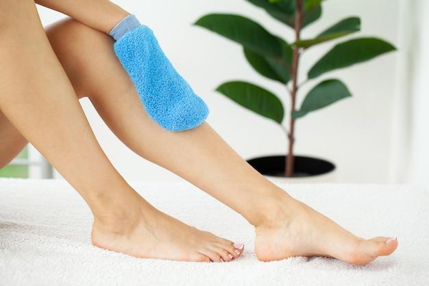 Vrouwenwapen dat blauwe droge borstel houdt om haar been te bedekken, cellulitisbehandeling en droog het borstelen. Premium Foto