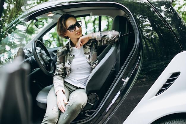 Vrouwenzitting binnen een auto in het bos Gratis Foto
