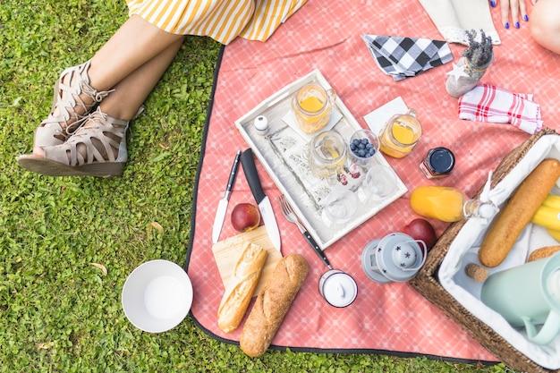 Vrouwenzitting dichtbij de snack op deken bij picknick Gratis Foto