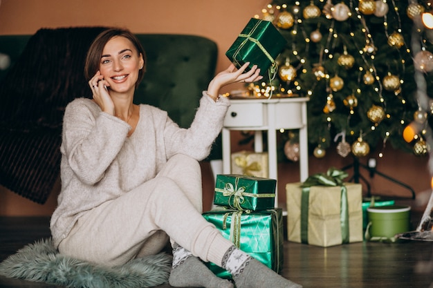 Vrouwenzitting door kerstboom en het winkelen op de telefoon Gratis Foto