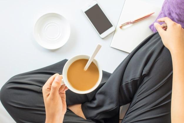 Vrouwenzitting en het drinken koffie met slimme telefoon en notitieboekje op witte vloer. bovenaanzicht. Premium Foto