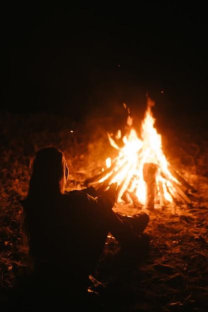 Vrouwenzitting en het worden warm dichtbij het vuur in het nachtbos Gratis Foto