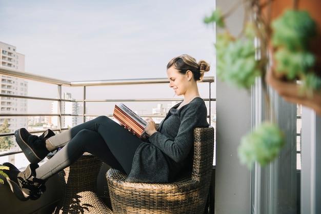 Vrouwenzitting in balkon die fotoalbum bekijken Gratis Foto