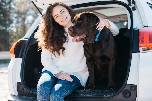 Vrouwenzitting met haar hond in open boomstam Gratis Foto