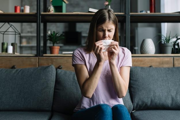 Vrouwenzitting op bank blazende neus met papieren zakdoekje Gratis Foto