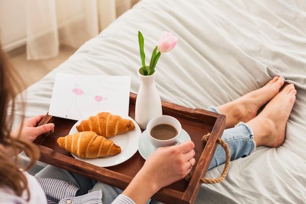 Vrouwenzitting op bed met koffie op dienblad Gratis Foto