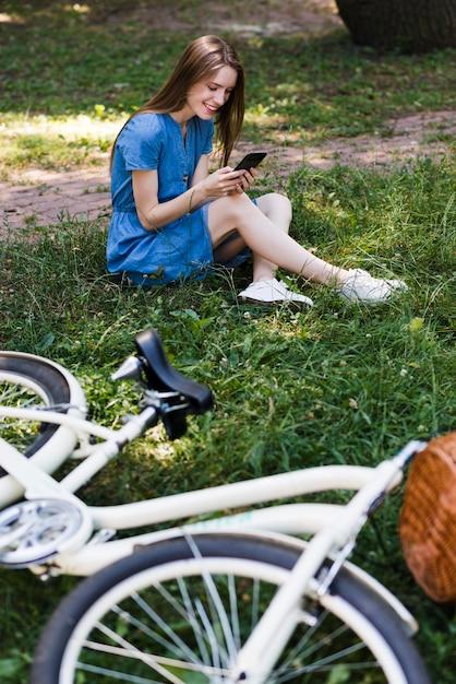 Vrouwenzitting op gras naast fiets Gratis Foto