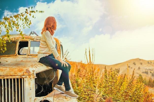 Vrouwenzitting op roestige oude klassieke vrachtwagen. jonge vrouw in een zomer veld zittend op oude auto. Premium Foto