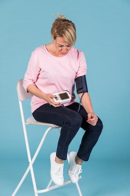 Vrouwenzitting op stoel die bloeddruk controleren op elektrische tonometer Gratis Foto