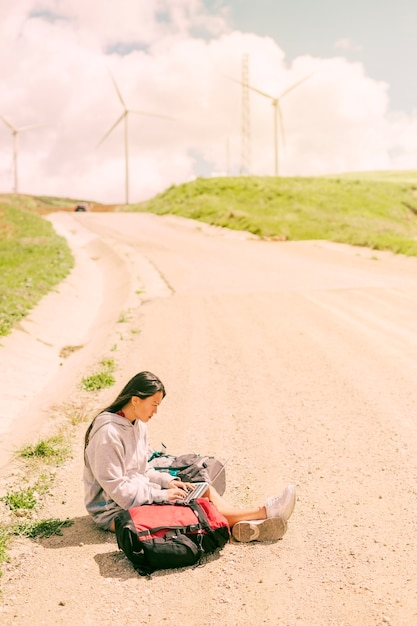 Vrouwenzitting op stoffige weg en het werken aan laptop onder rugzakken Gratis Foto