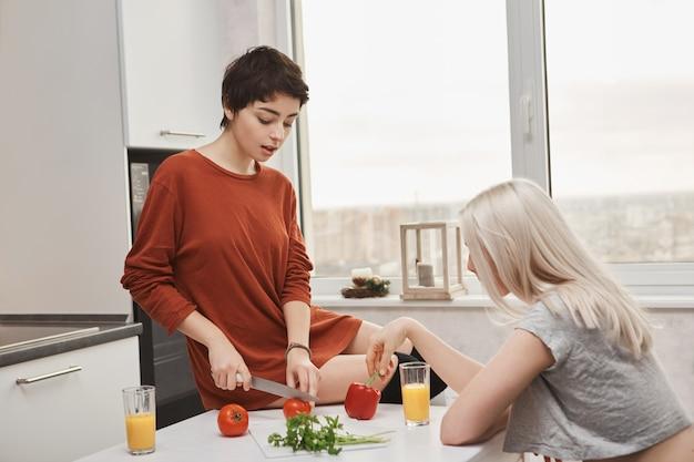 Vrouwenzitting op tomotoes van de lijstknipsel terwijl haar vriend jus d'orange drinkt Gratis Foto