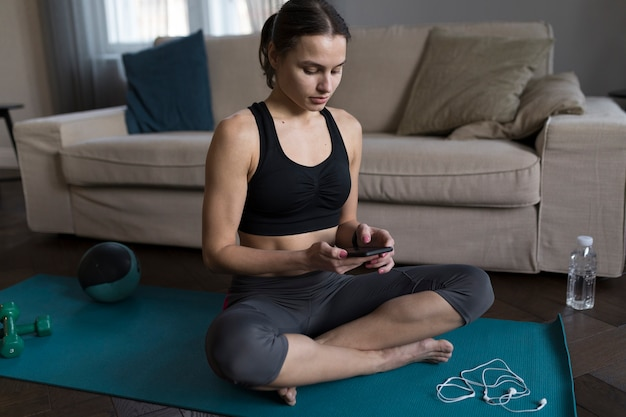 Vrouwenzitting op yogamat en het bekijken telefoon Gratis Foto