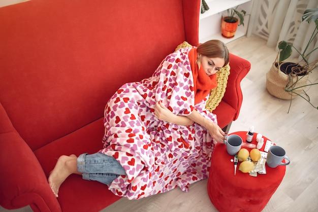 Vrouwenzitting thuis met een koude en het drinken hete thee Gratis Foto