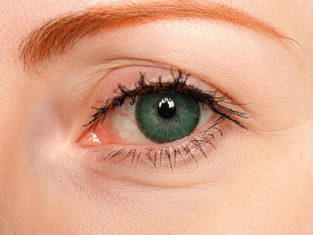Vrouwtje links blauw oog getint in groene kleur met speciale contactlens close-up Premium Foto