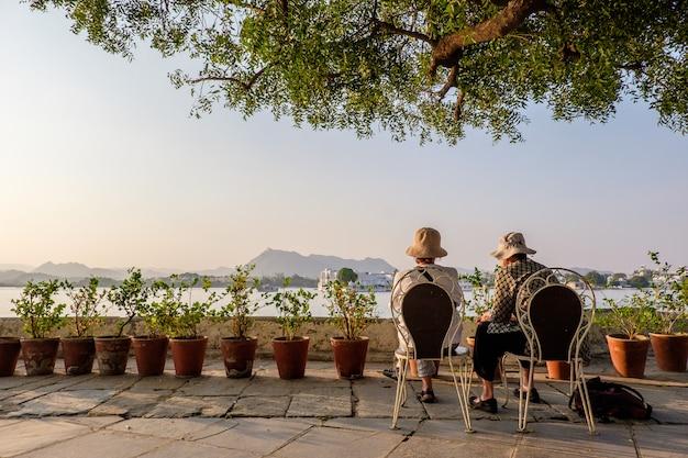 Vrouwtjes die hoeden dragen die op stoelen dichtbij bloempotten zitten die de bergen in de verte bekijken Gratis Foto