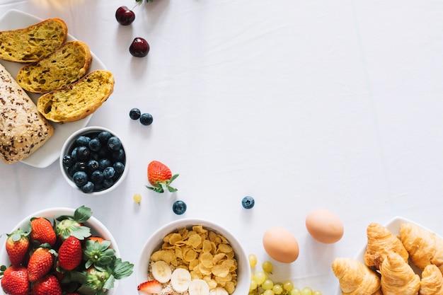 Vruchten; gebakken brood en croissant op witte achtergrond Gratis Foto