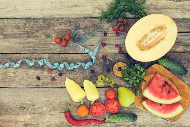 Vruchten, groenten en in maatregelenband in dieet op houten achtergrond. getinte afbeelding. Premium Foto