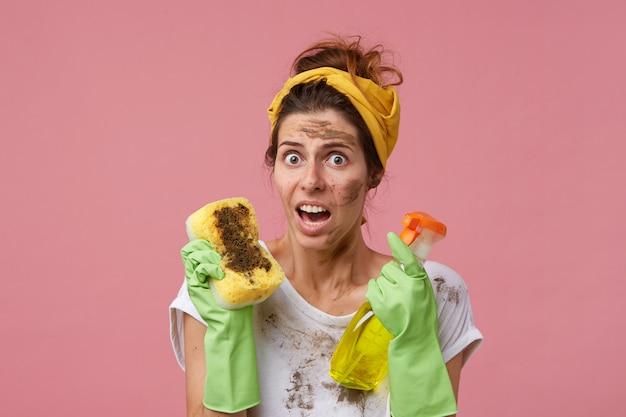 Vuile huishoudster doet de voorjaarsschoonmaak met rubberen beschermende handschoenen en een hoofdband op het hoofd, kijkend met geïrriteerde en verbaasde blik die stof en schoonmaak haat. huishoudelijk werk en klusjes Gratis Foto