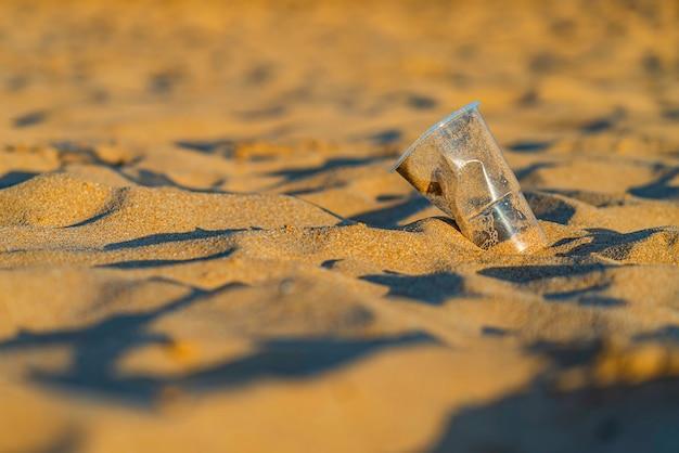 Vuilnis plastic beker op het gouden strandzand van de oceaan, playa de las teresitas, tenerife. bescherming van het milieu concept. verontreiniging van oceanen met plastic afval. recyclen. Gratis Foto