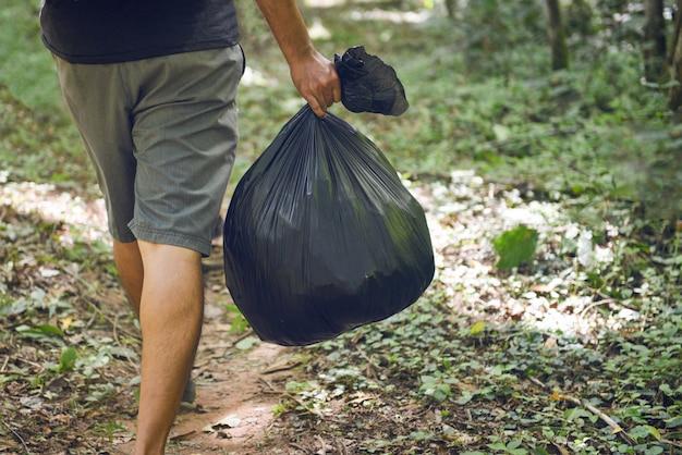 Vuilnisinzameling ecologie mensen schoonmaken van het park, man hand met zwarte plastic vuilniszakken Premium Foto