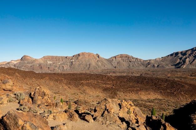 Vulkanische rode grondkrater met heldere hemel Gratis Foto