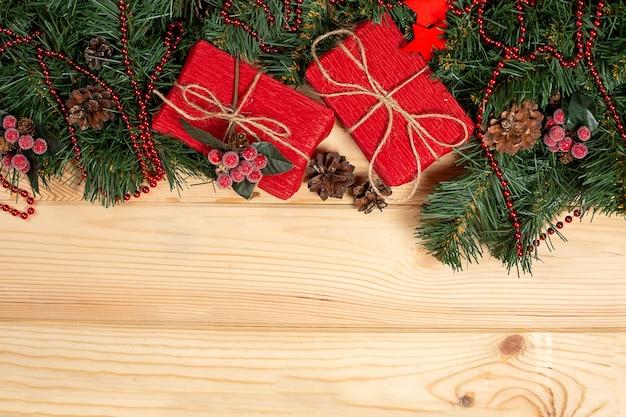 Vuren takken met kerst ornamenten en cadeau op houten Premium Foto