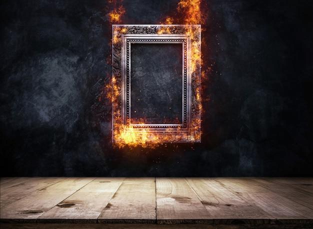 Vuur brandende zilveren antieke fotolijst op donkere grunge muur met houten tafelblad, leeg klaar voor productvertoning of montage. Premium Foto