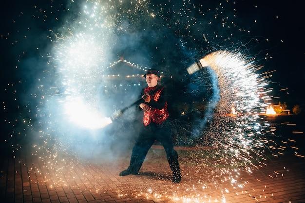 Vuur show. een man spint brandende fakkels Premium Foto
