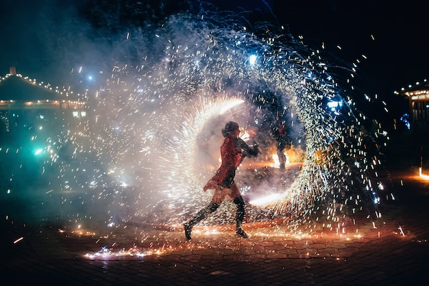 Vuur show. het meisje draait vurige fonkelende fakkels Premium Foto