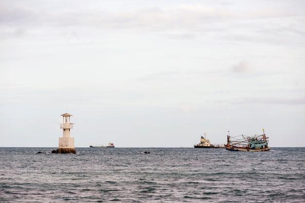 Vuurtoren en schip in de zee. Premium Foto
