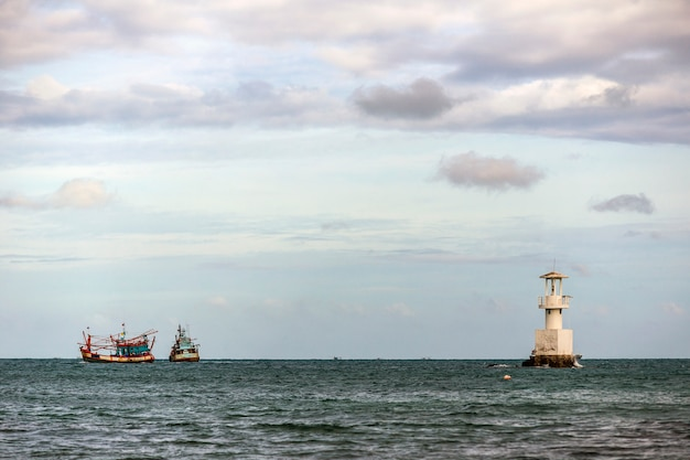 Vuurtoren en vissersboot in de zee. Premium Foto
