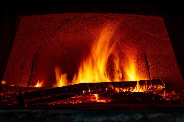 Vuurvaste bakstenen pizzaoven die bestand is tegen hoge temperaturen met brandhout dat wordt verbrand en voorbereid voor het bakken van pizza's. Premium Foto