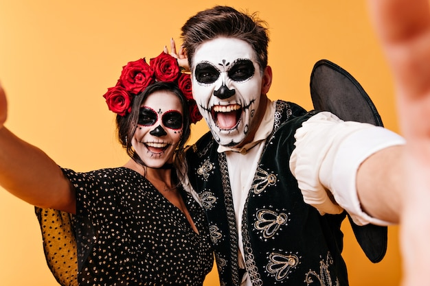 Waanzinnige, grappige jonge man en vrouw nemen selfies en pronken met hun skeletmake-up. meisje met bloemen op haar hoofd en haar vriend hebben plezier Gratis Foto